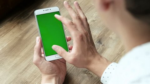 One modern businessman use the handheld cellphone with greenscreen chromakey, gesturing closeup in workplace at wooden desk. Guy hold cellular portable device, scrolling and tapping by surfing web