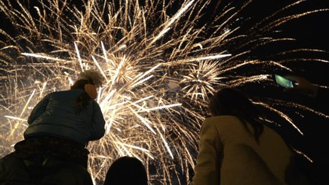 Little girl sitting on your dad's shoulders and watching fireworks. Concept of family relationships and Father's day. Viewers take pictures on smartphone.le of any holiday