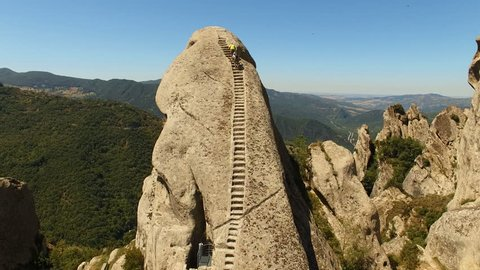 Two people climbing a mountain with a staircase engraved on its surface. Aerial shot. About sports, lifestyle, well-being, path, height, dizziness, fatigue, obstacles, overcoming an obstacle