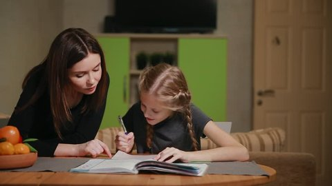 Mother and daughter doing a school homework assignment. Mom helps to deal with it.