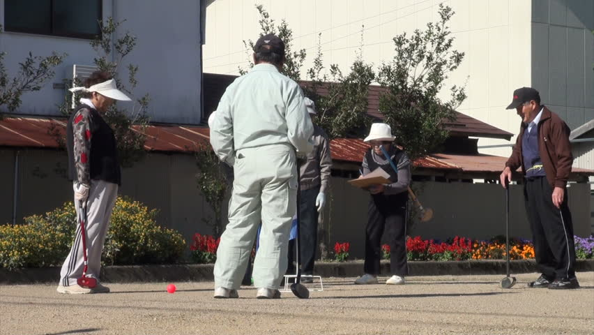 TAKAYAMA, JAPAN - 19 OCTOBER 2012: Senior citizens are playing a game of 'gateball', a popular pastime among the elderly in Japan