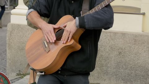 MUNICH, GERMANY, SEPTEMBER 15, 2017: Street musician playing on acoustic guitar. Slow Motion in 96 fps. Street Guitarist Playing on the Street