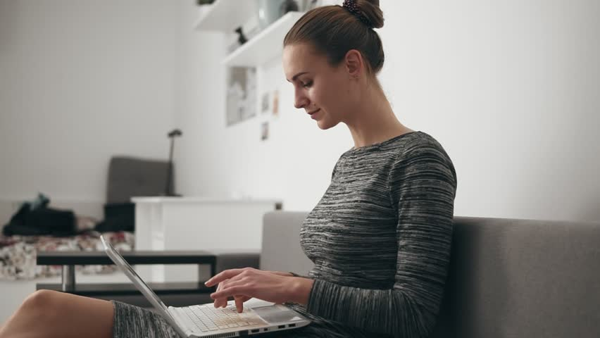 Side view of young woman at home sitting on the sofa, working with a laptop and typing text fast looking at the screen | Shutterstock HD Video #32499937