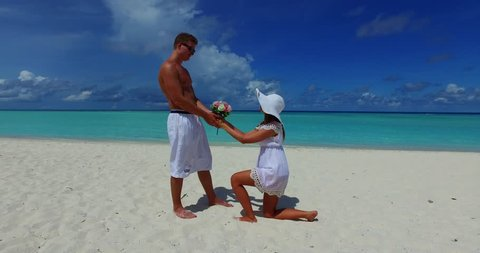 v14868 two 2 people proposal marriage romantic young couple holding hands on a tropical island of white sand beach and blue sky and sea