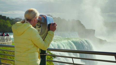 A woman looks at Niagara Falls through a coin operated binoculars