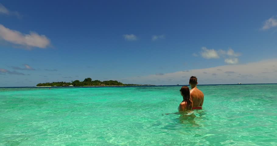 v15496 two 2 people together having fun man and woman together a romantic young couple sunbathing on a tropical island of white sand beach and blue sky and sea