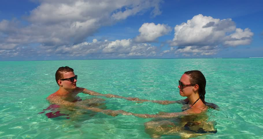 v15520 two 2 people together having fun man and woman together a romantic young couple sunbathing on a tropical island of white sand beach and blue sky and sea