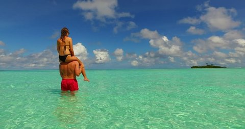 v15478 two 2 people together having fun man and woman together a romantic young couple sunbathing on a tropical island of white sand beach and blue sky and sea