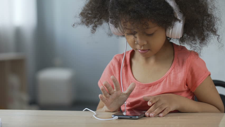 Beautiful child with headset listening to music and viewing photos on cellphone