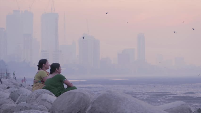 Two middle aged women sitting on tetra-pods and chatting next to the seashore. While city skyline visible in background in the morning, Mumbai, India (2017)