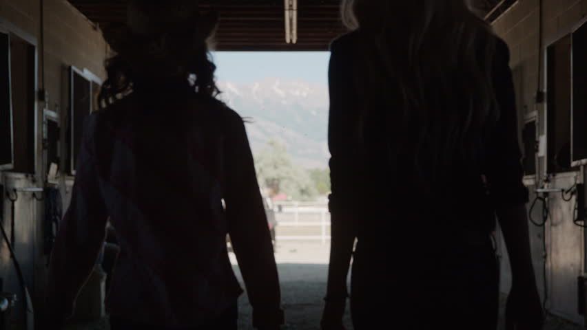 Wide slow motion silhouette of woman and girl leaving stable / Lehi, Utah, United States