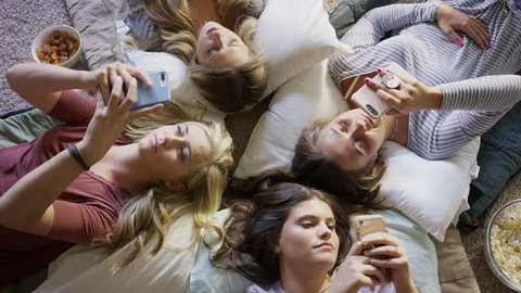 Medium high angle shot of girls laying on floor distracted by cell phones / Cedar Hills, Utah, United States