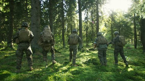 Squad of Five Fully Equipped Soldiers in Camouflage on a Reconnaissance Military Mission, Rifles Ready. They're Moving in Formation Through Dense Forest. Following Back View Shot. 4K UHD.