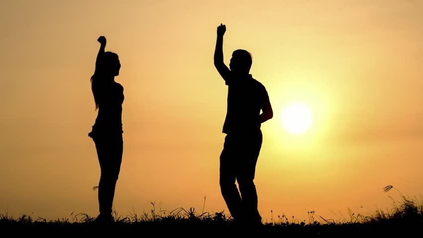 silhouette of young people excited jump and give five