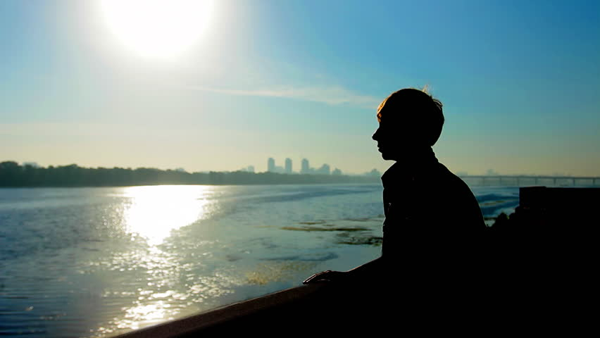 young guy near wide river and far away city, silhouette against sunrise #3262135