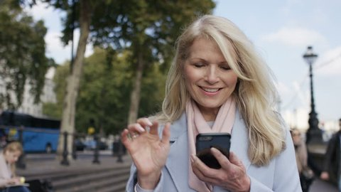 Attractive mature female walking and texting on her phone, in slow motion