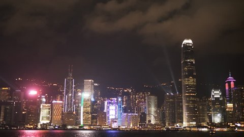 a night view of a light show at the ifc building and victoria harbour -as seen from tsim sha tsui promenade in hong kong, china
