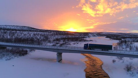 AERIAL: Flying above semi truck driving along scenic countryside highway at sunset. Transporter lorry crossing a bridge above frozen icy river in picturesque snowy landscape at gorgeous golden sunrise