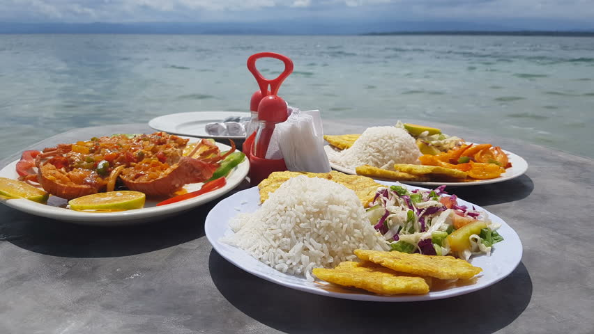 Closeup view of caribbean food served in table on the beach.