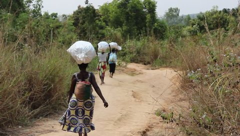 Three women carry heavy sacks on their heads in a small village near Kasangulu, outskirts of Kinshasa, Democratic Republic of Congo. July 2015