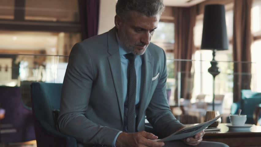 Mature businessman reading newspapers in a hotel lobby. Slow motion.