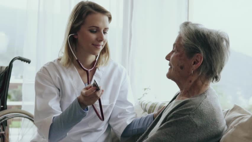 Health visitor and a senior woman during home visit. A female nurse or a doctor examining a woman. Slow motion.