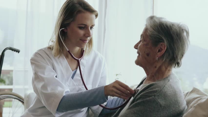 Health visitor and a senior woman during home visit. A female nurse or a doctor examining a woman. Slow motion. #32667007