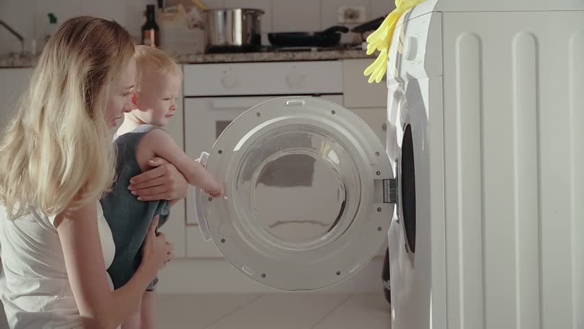 Young mother holding baby on hands and using washing machine. Young mom putting dirty laundry in washing machine