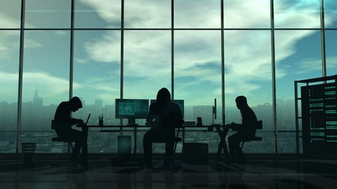 Dark silhouettes of hackers at work on a background of a gloomy city. Displays the virtual online crimes and cyber attacks.