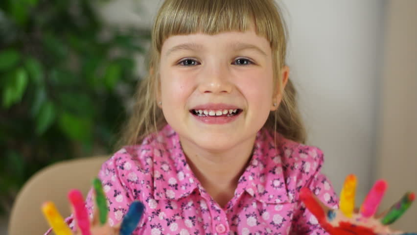 Closeup portrait funny girl coloring. Girl covered in finger paint. Selective focus.