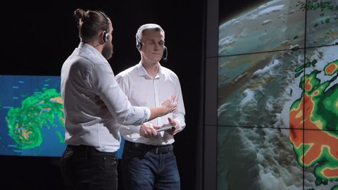 Two researchers in development center monitoring behavior of hurricane exploring live map changes. Elements of this image furnished by NASA.
