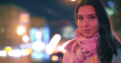 Beautiful young woman in night city, illuminated by colorful neon lights, looking at camera. Shallow DOF, blurred city traffic in background.
