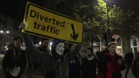 UK Nov 2017 - Protestor wearing a Guy Fawkes mask marches holding a Diverted Traffic road