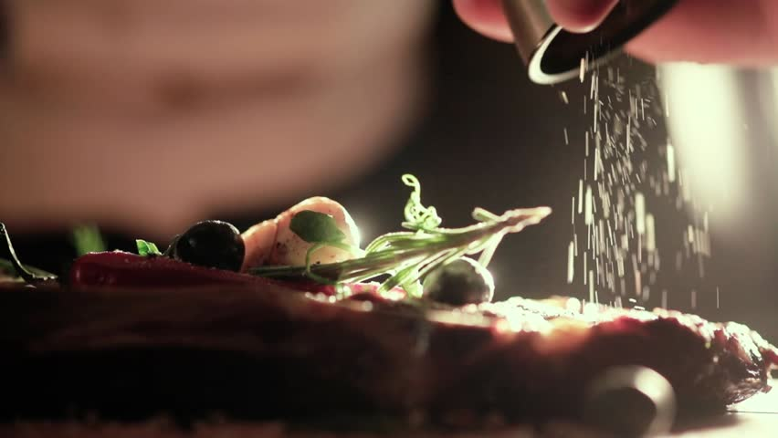 Extreme Close Up view of a Hand Seasoning Cooked piece of Meat in a Bright Light. Chef Accompanying Steak with Garlic, Rosemary, Pepper, Salt. Delicious, Modern Cuisine, Exclusive Recipe. 120 fps. #32709067