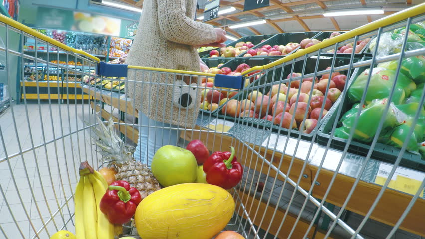 Woman with cart or trolley buying fresh vegetables and fruits at supermarket. Point of view shot. Consumerism, sale, shopping and health care concept | Shutterstock HD Video #32711533