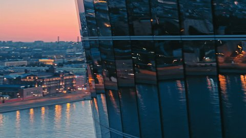 Windows of futuristic metal and glass skyscraper building at evening