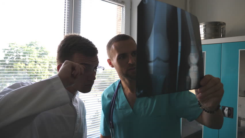 Two caucasian doctors view mri picture and discussing about it. Medical workers in hospital examine x-ray prints. Male medics consult with each other while looking at x ray image. Close up #32719207