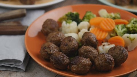 Pouring cream sauce onto Swedish meatballs with steamed vegetables