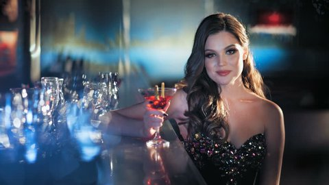 Beauty young brunette woman sitting at the bar with glass of wine in luxury interior