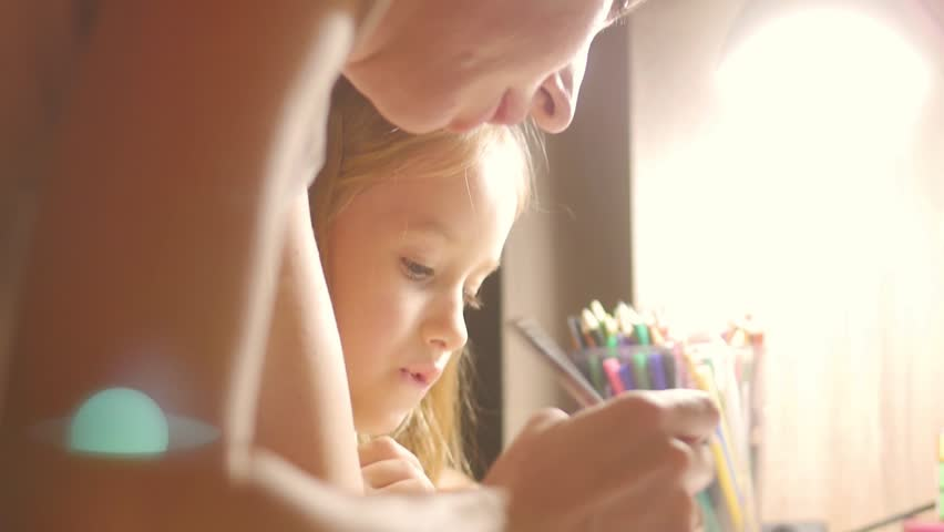 Young mother helps her daughter with her homework at on the table under the light of a lamp. | Shutterstock HD Video #32730967