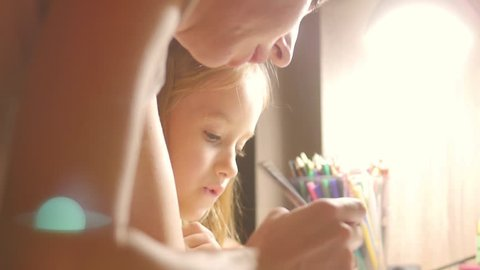 Young mother helps her daughter with her homework at on the table under the light of a lamp.