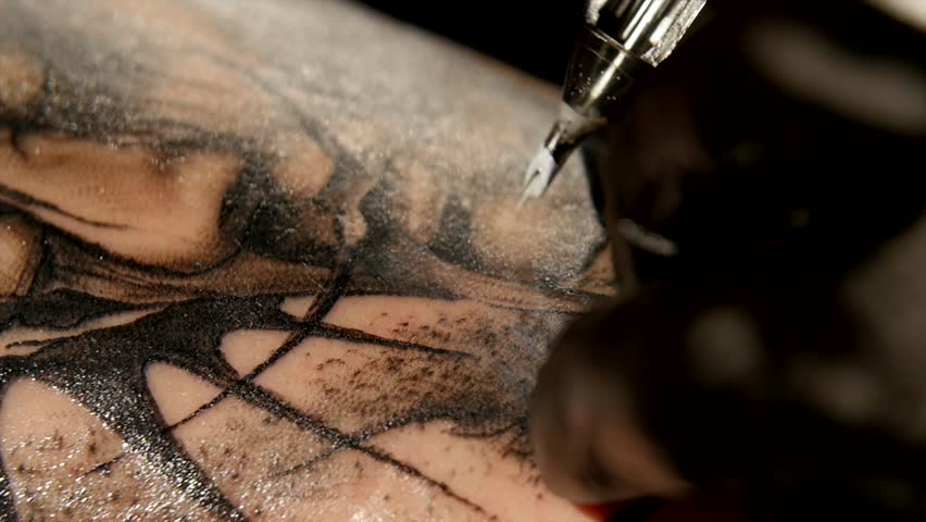 Tattoo artist make tattoo in studio, tattooing on the body. close up