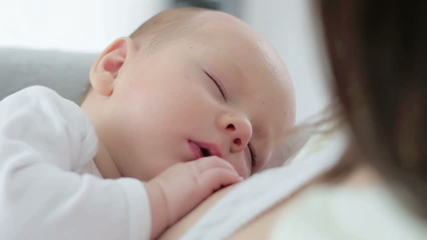Newborn baby sleeping peacefully over the mother chest | Shutterstock HD Video #32745397