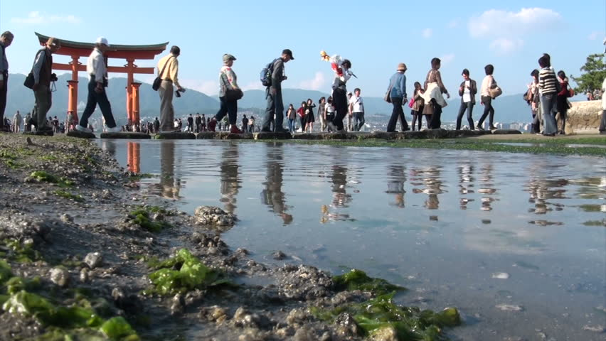 MIYAJIMA, JAPAN - 28 OCTOBER 2012: A tour group cross a stream leading up to the Miyajima 'floating torii gate' during low tide in Japan