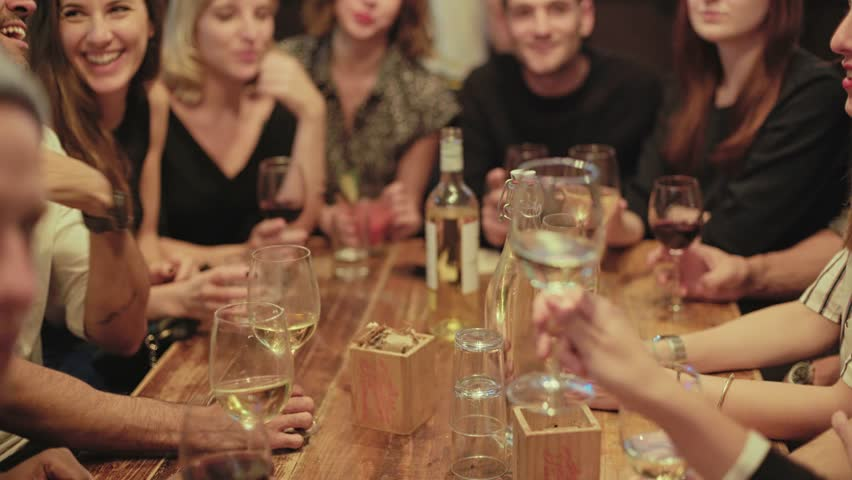 Group of happy, smiling and positive, drunk friends drink and cheer their glasses at party or reunion in middle of crowded popular hipster bar. They laugh and celebrate friendship or new year