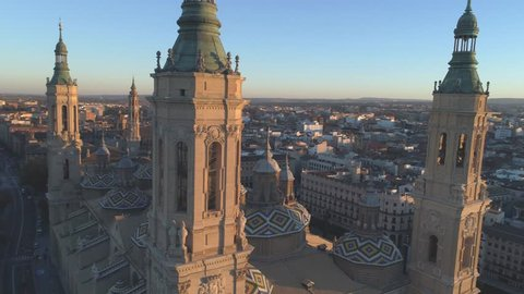 Flying above the Cathedral of the Pillar in Zaragoza at sunset, aerial landscape 4k