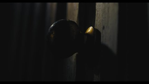 Pushing a door open in a dark, creepy setting. Ghost story, horror, thriller set. Close up on the door knob