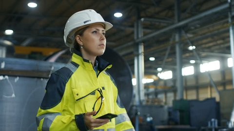 Female Industrial Worker in the Hard Hat Uses Mobile Phone While Walking Through Heavy Industry Manufacturing Factory. In the Background Various Metalwork Project Parts Lying. Shot on RED EPIC-W 8K