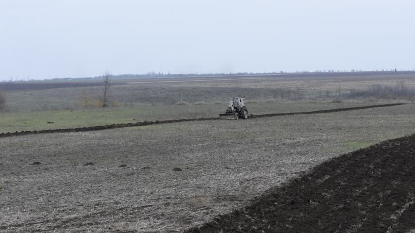 The farmer plows his field with an old tractor with one plow. Autumn work in the field. Eastern Europe, Ukraine, Moldova.