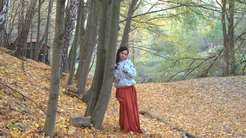 young attractive ukrainian girl in modern ethnic clothes on a background of golden trees and a long olive tree. on the ground lie the leaves of the leaves. The girl is wearing a knitted sweater. warm